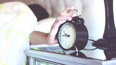Man die vanuit bed zijn wekker uit doet en moeite heeft met opstaan