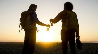 Twee mannen op het strand die onder de zonsondergang een biertje drinken.