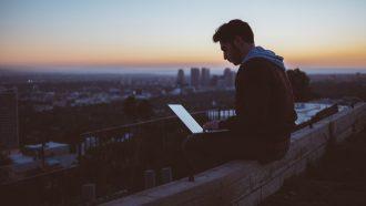 man werkt aan side hustle bij zonsondergang